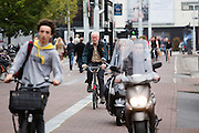 In Amsterdam rijden scooters tussen de fietsers over fietspad. De Fietsersbond wil samen met de gemeente Amsterdam dat bromscooters niet meer op het fietspad mogen rijden. De scooters veroorzaken veel overlast op de toch al volle fietspaden in de hoofdstad. Volgens onderzoek is het veiliger om de scooters op de hoofdrijbaan te laten rijden. Bovendien is het voor fietsers ongezond als de bromscooters met hun uitlaatgassen op het fietspad rijden. <br /> <br /> In Amsterdam scooters ride between the cyclists on the bike lane. The Dutch Cyclists Union and the municipality of Amsterdam want that moped scooters no longer allowed to ride on the bike lane.  The scooters are a nuisance to the already full bicycle lanes in the capital. According to research, it is safer to drive scooters on the main carriageway. Moreover, it is unhealthy for cyclists that moped scooters with their pollutions ride on the bike path.