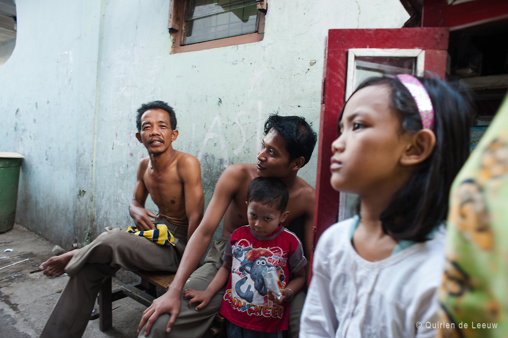A Javanese family sitting in front of there house in Jakarta city center