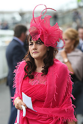 © Licensed to London News Pictures. 09/04/2016. Liverpool, UK. A brightly dressed woman at Grand National day of the Grand National 2016 at Aintree Racecourse near Liverpool. The race, which was first run in 1839, is the most valuable jump race in Europe. Photo credit : Ian Hinchliffe/LNP