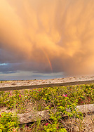 Sunset adds a golden glow to the clouds above a rainbow at West Dennis Beach.