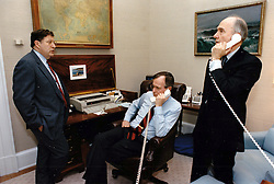 United States President George H.W. Bush speaks with US Secretary of State James A. Baker, III, from his study in the Oval Office of the White House in Washington, DC on January 17, 1991. Pictured from left to right: White House Chief of Staff John Sununu, the President, and National Security Advisor Brent Scowcroft.<br /> Photo by David Valdez / White House via CNP/ABACAPRESS.COM