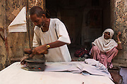 'Ironing Man' Indian man ironing clothes for a living with coal iron in market.<br /> Bharatpur town. Rajasthan. INDIA