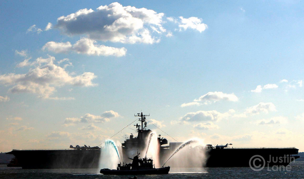 Tugboats tow the Intrepid Sea, Air & Space Museum, a decommissioned  United States aircraft carrier, through New York Harbor on the way to a pier in New Jersey as a fire boat (foreground) passes by on Tuesday 05 December 2006.
