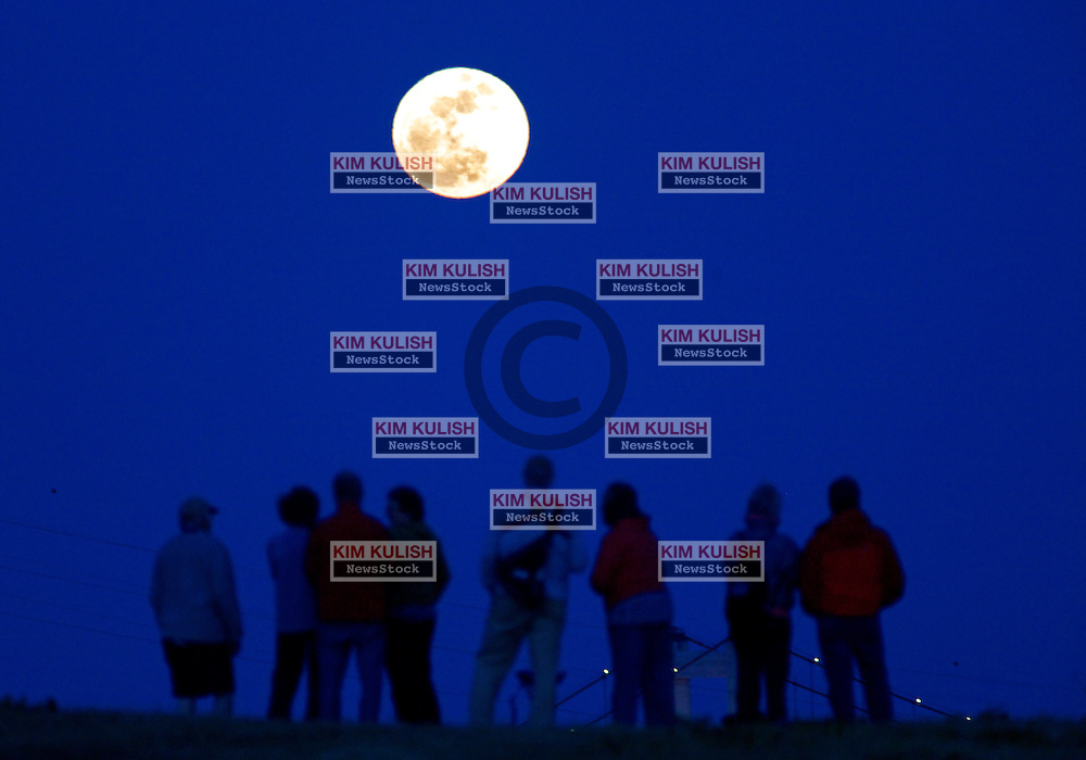 """A group of people watch as a Perigee Moon rises over the Alfred Zampa Memorial Bridge spanning the Carquinez Strait in Vallejo, California.  The """"Supermoon"""" appears 14 percent larger and 30 percent brighter as it makes it's closest approach to the earth this year."""