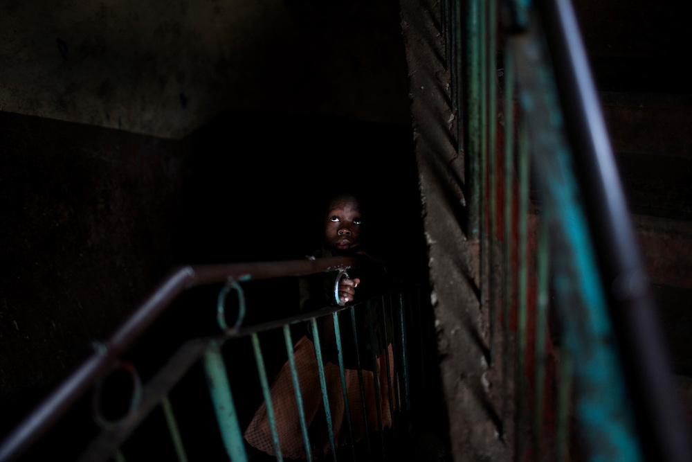In the dark stairway of a building in Mathare, one of the poorest slums in Nairobi.  Running water and electricity are scarce and trash and human waste fills the streets.  Many people have no jobs and those who do work can earn less than one dollar a day.