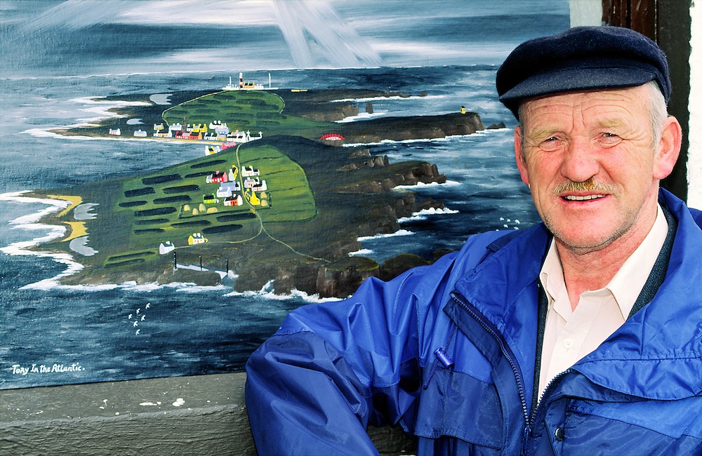 Patsy Dan Rodgers, the King of Tory Island, Donegal, Ireland. Musician and artist seen with one of his paintings of the island.