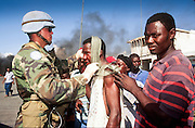 12 FEBRUARY 1996, PORT AU PRINCE, HAITI: US peacekeeping soldier assigned to the UN mission in Haiti helps a Haitian man injured in a melee on the street in the port area of Port au Prince, Haiti, February, 1996.  PHOTO BY JACK KURTZ