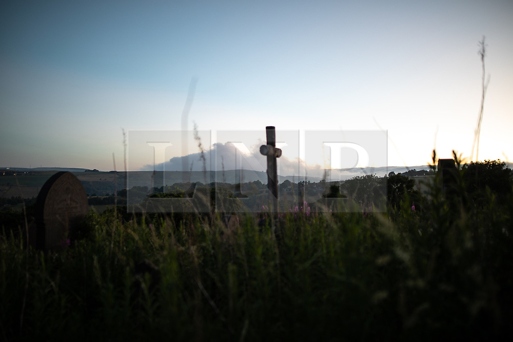 "© Licensed to London News Pictures . 28/06/2018 . Saddleworth , UK . View of smoke on hills across Saddleworth moor as viewed from Saddleworth Graveyard , where fire burned through dry grass in the late hours of Wednesday 27th June (yesterday) and had to be extinguished by firefighters . The army are being called in to support fire-fighters , who continue to work to contain large wildfires spreading across Saddleworth Moor and affecting people across Manchester and surrounding towns . Very high temperatures , winds and dry peat are hampering efforts to contain the fire , described as "" unprecedented "" by police and reported to be the largest in living memory . Photo credit: Joel Goodman/LNP"