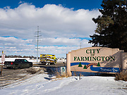 """26 FEBRUARY 2020 - FARMINGTON, MINNESOTA: The sign welcoming people to Farmington, MN, about 30 minutes south of the Twin Cities. Farmington, with a population of 21,000, is a farming community that has become a Twin Cities suburb, the population has doubled since the 2000 census. The city lost its only grocery store, a Family Fresh Market, in December, 2019. The closing turned the town into a """"food desert."""" The USDA defines food deserts as having at least 33% or 500 people of a census tract's population in an urban area living 1 mile from a large grocery store or supermarket. Grocery chains Hy-Vee and Aldi both own land in Farmington but they have not said when they plan to build or open stores in the town.     PHOTO BY JACK KURTZ"""