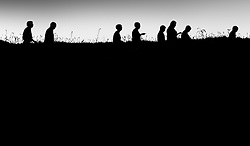 The silhouette of people walking along a path on East Pentire Headland in Newquay, Cornwall.