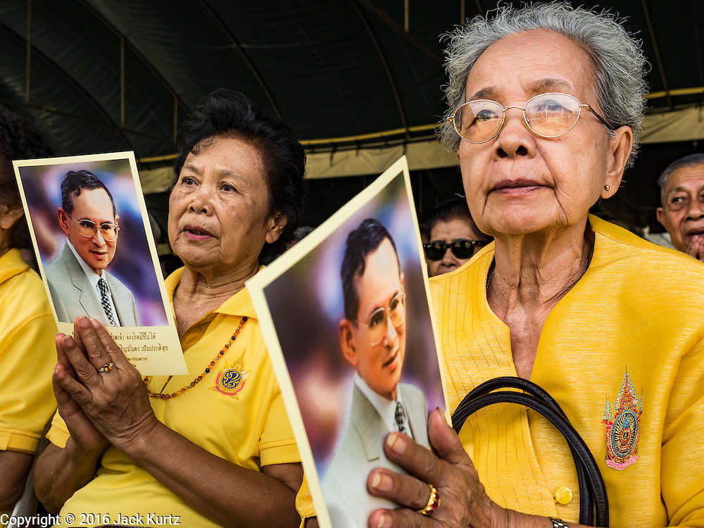 09 JUNE 2016 - BANGKOK, THAILAND:  Women hold pictures of Bhumibol Adulyadej, the King of Thailand, while they pray for him after an alms giving ceremony at the Grand Palace Thursday. Thailand marked 70 years of the reign of Bhumibol Adulyadej with a special alms giving ceremony for 770 monks in front of the Grand Palace in Bangkok. The King, also known as Rama IX, ascended the throne on 9 June 1946. He is the longest serving monarch in Thai history and the longest serving monarch in the world today. He is revered by most Thais and is widely seen as a unifying figure in the country.    PHOTO BY JACK KURTZ