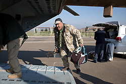 © Licensed to London News Pictures. 11/12/2014. Fishkhabour, Iraq. A machine gun armed fighter of the Iraqi-Kurdish peshmerga climbs into an Iraqi Air Force Mi-17 Hip helicopter as he heads for Mount Sinjar.<br /> <br /> Although a well publicised exodus of Yazidi refugees took place from Mount Sinjar in August 2014 many still remain on top of the 75 km long ridge-line, with estimates varying from 2000-8000 people, after a corridor kept open by Syrian-Kurdish YPG fighters collapsed during an Islamic State offensive. The mountain is now surrounded on all sides with winter closing in, the only chance of escape or supply being by Iraqi Air Force helicopters. Photo credit: Matt Cetti-Roberts/LNP