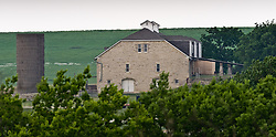 The massive 60 x 110 foot three-story limestone barn on the Spring Hill Farm and Stock Ranch located in the Tallgrass Prairie National Preserve in the Kansas Flint Hills was built by cattleman Stephen F. Jones. The bottom level is built into the side of a hill for insulation and the second level is even with the top of the hill for access. The 10,894-acre Tallgrass Prairie National Preserve is located in Chase County near the towns of Strong City and Cottonwood Falls. Less than four percent of the original 140 million acres of tallgrass prairie remains in North America. Most of the remaining tallgrass prairie is in the Flint Hills in Kansas. Tallgrass Prairie National Preserve is the only unit of the National Park Service dedicated to the preservation of the tallgrass prairie ecosystem. The Tallgrass Prairie National Preserve is co-managed with The Nature Conservancy.