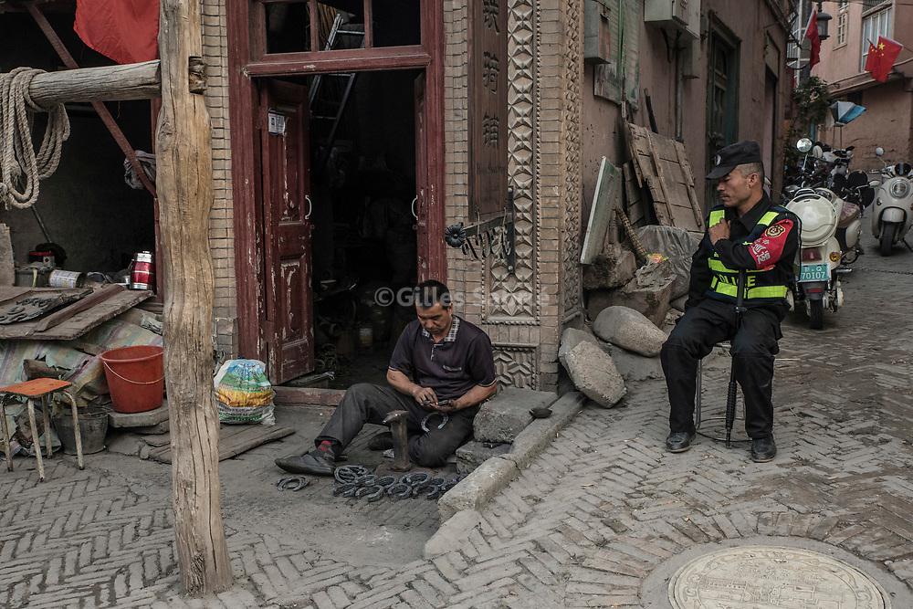 Kashgar. October 1st, 2017<br /> A blacksmith under watch of a police guard.
