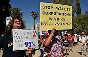 """Dee Hill-Zuganelli, (left), and Teena Cross, along with about 1,000 demonstrators, participate in Occupy Tucson at Military Plaza in Armory Park, Tucson, Arizona, USA.  The Occupy Tucson organizers created the movement in solidarity with the Occupy Wall Street movement in New York and the Occupy Together movement across the USA.  Hill-Zuganelli said, """"This is about the 99%.  All colors and ages are here.  I am glad people are standing up against the economic elite.""""  Coss said, """"I am here because I believe in the fact that Wall Street has taken over and we the people who support the government are being left in the dust.""""..The leaders of this movement are the everyday people participating in a movement with many de-centralized goals, with an over-arching theme of protesting government corruption from corporate money and national income disparity. We use a tool called the """"General Assembly"""" to facilitate open, participatory and horizontal organizing between members of the public. We welcome people from all colors, genders and beliefs to participate in our movement. .."""