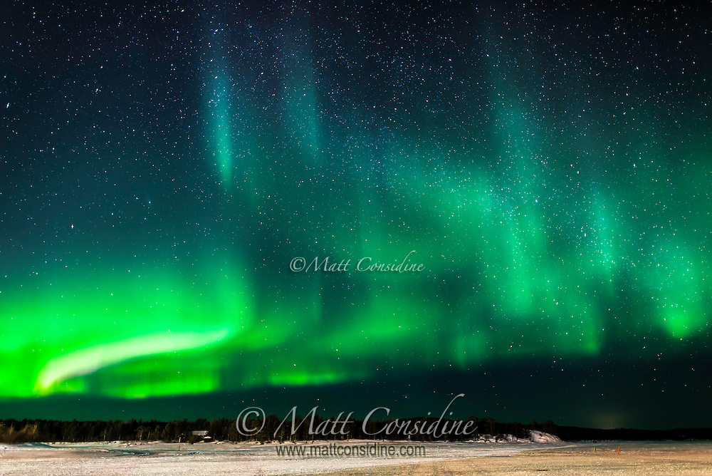 Strong green curtain aurora over ice lake, (Photo by Travel Photographer Matt Considine)