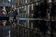 Financial services women walk through reflected light from a nearby skyscraper in the City of London, the capital's financial district aka the Square Mile, on 17th May 2018, in London, UK.