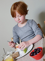 7-8 year old sits eating boiled egg