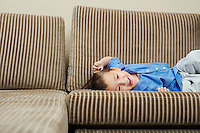Boy relaxing on sofa in living room