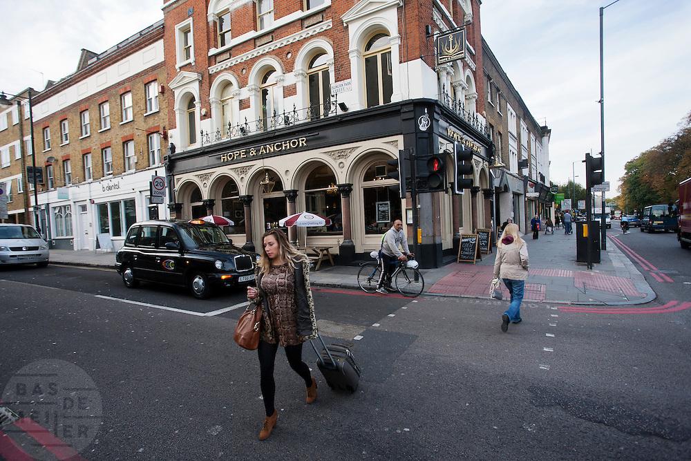 Een vrouw steekt de straat over in de Londense wijk Islington.<br /> <br /> A woman is crossing the street in London district Islington.