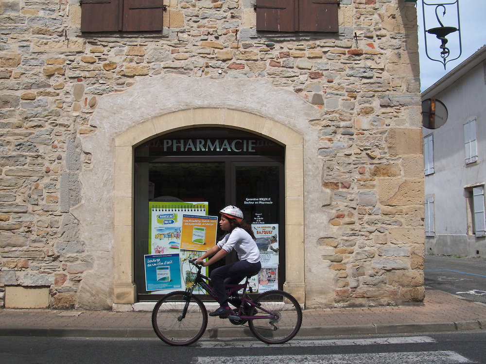 A young girl hurries through the town by bike in the fortified town of Navarrenx in France's Pyrenees-Atlantiques region.