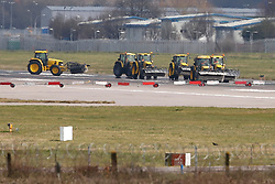 © Licensed to London News Pictures. 29/02/2016. Gatwick, UK. Tractors with cleaning equipment attached to the front on the runway at Gatwick Airport in West Sussex, where the main runway has been closed due to a spillage.  Photo credit: Peter Macdiarmid/LNP