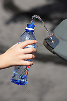 hand filling up water in a plastic bottle at a public spring fresh water fountain in paris
