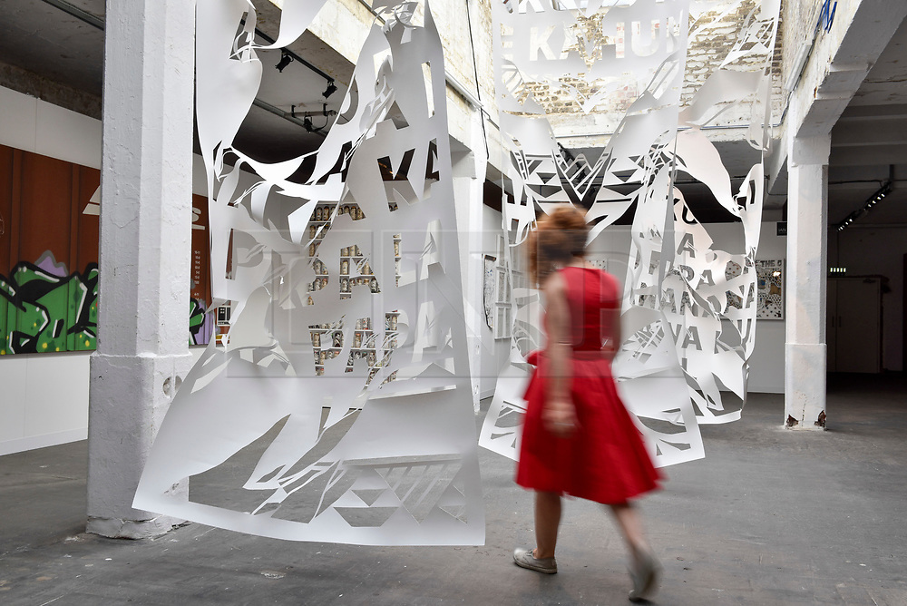 © Licensed to London News Pictures. 06/10/2017. London, UK.  A woman walks through an installation of hand cut paper by Ian Kual'i at the Moniker Art Fair, the world's biggest urban art fair, taking place at the Old Truman Brewery in East London from 5 to 8 October 2017.  The fair brings together the world's most influential new-contemporary and urban art galleries to show international artworks to Londoners. Photo credit : Stephen Chung/LNP