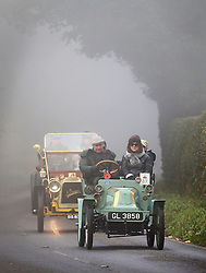 © Licensed to London News Pictures. 01/11/2015. Staplefield, UK. A 1901 Darracq leads a 1903 Clement along a foggy road near Staplefield as it takes part in the London to Brighton Veteran Car Run.  Photo credit: Peter Macdiarmid/LNP