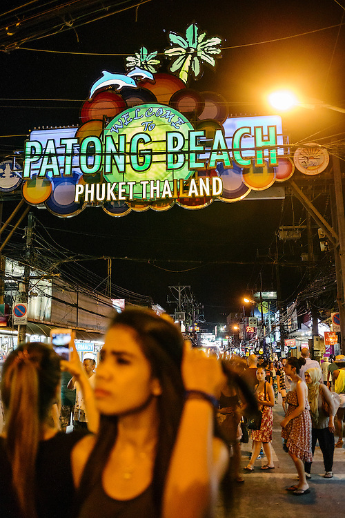 The end of Bangla Street is greeted with a sign introducing Patong beach. A lady boy and tourists wander along the street.