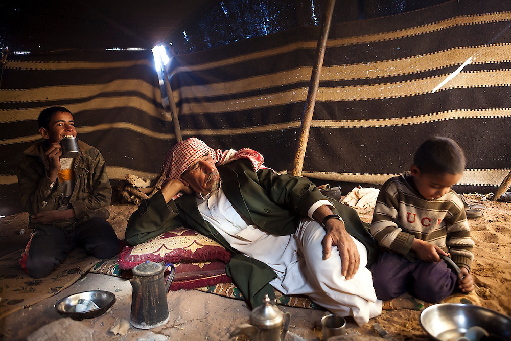 A Bedouin patriarch sleeps surrounded by two of his many sons in his remote home encampment in Wadi Rum, Jordan.