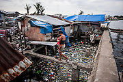 A woman carries her baby at Magallanes neighbourhood on June 11 2014 in Tacloban, Philippines. Tacloban city and the surrounding villages were devastated after typhoon Hayan passed over leaving at least 6,200 people dead and a high number of disappeared on November 8, 2013.