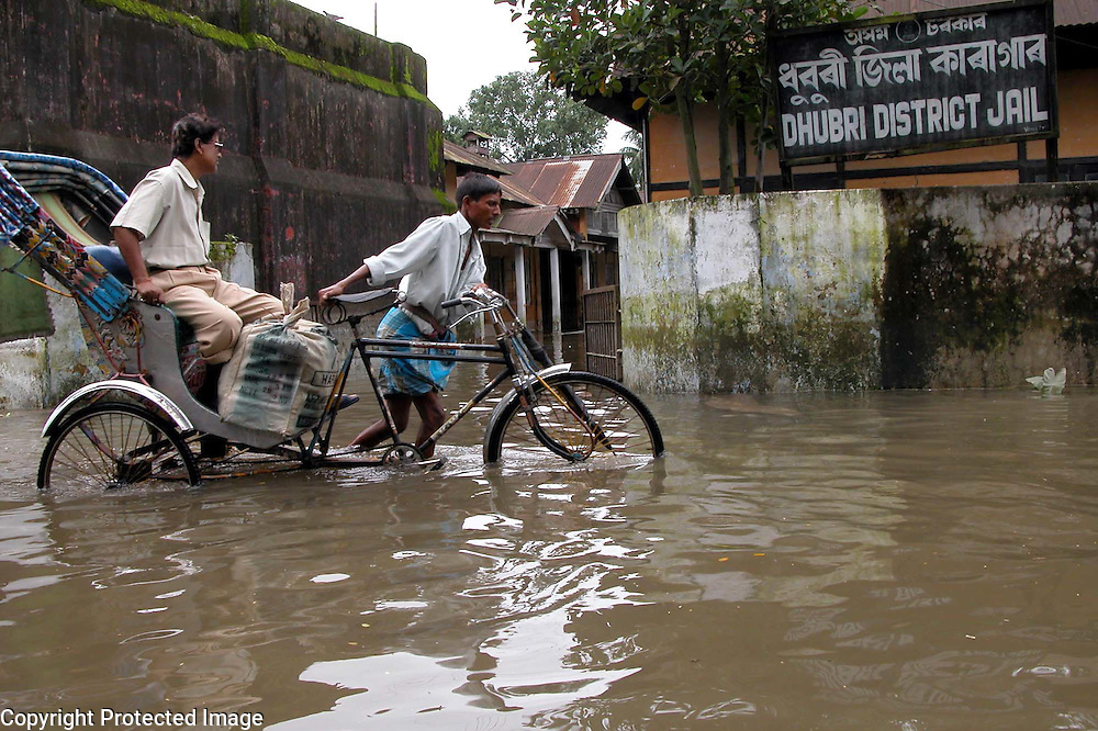 A rickshawpullar is passing near the district jail that inundated by floodwaters at Dhubri village, about 299 kilometers  southwest of Gauhati, capital of northeastern Indian state of Assam, Saturday, July 24, 2004,  while 193 hardcore convicts and extremists are evacuated and shifted to a higher place after the floodwaters submerged the jail areas, said the jail authorities.. .Floodwaters of the Asia's one of the largest river, Brahmaputra and its 35 tributaries have affected more than one million in all of Indian subcontinent and disrupted communication in many parts of the India and Bangladesh, sources said. (AP Photo/Shib Shankar Chatterjee).