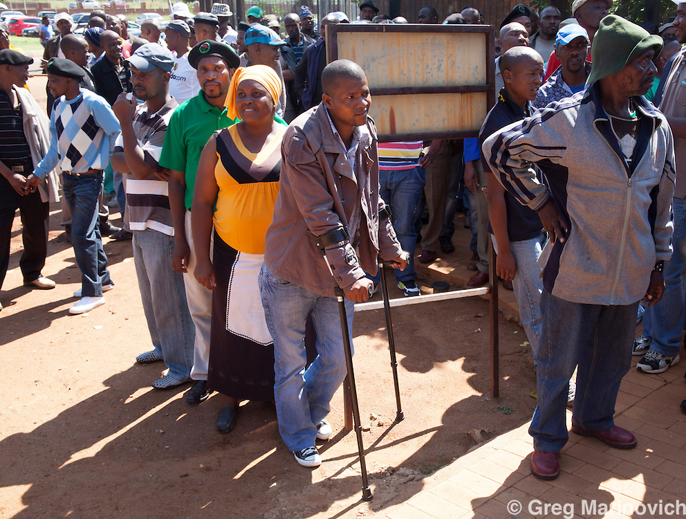 Wonderkop, Marikana, North West South Africa Feb 12, 2013. Mzoxolo Magidiwana, on crutches, claims the police shot him while he lay wounded at Marikana on Aug 16th. The 276 miners who were arrested following the Marikana massacre of August 16 1012 and their supporters travel to Garankuwa magistrates court on charges of public violence. Their court date was postponed to October. Photo Greg Marinovich