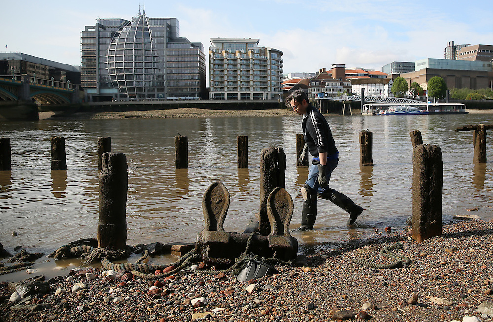Mudlarker Jason Sandy looks for items on the bank of the river Thames in London, Britain May 22, 2016. When the river Thames is at low tide, mudlarkers scour the shore for historical artefacts and remains from there City of London's ancient past. Finds can date back to Roman times to when the city was found up until more recent times. Anyone can walk along the river and look for finds, but the uses of metal detectors and digging is restricted. Mudlarkers need to be licences by the Port of London Authority. All find should be register with the Museum of London. REUTERS/Neil Hall
