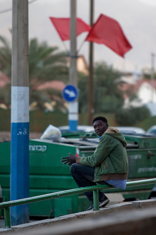 "A Sudanese refugee seats under red flags in the city of Eilat on  February 28 2011. The municipality hung 1,500 red flags around the city as a sign of warning and put up hundreds of banners reading: ""Protecting our home, the residents of Eilat are drawing the line on infiltration."" Eilat Mayor Meir Yitzhak Halevi said that 10 percent of the city's population was currently made up of migrants and that the residents feel that the city has been conquered...Photo by Olivier Fitoussi."