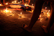 """Velatione"" on a Chilean patient in Quiballo, near the holy mountain of Sorte, Venezuela. The ""Velatione"", from the Spanish ""vela"", meaning candle, is a cure, purification and energy recharge rite. The patient lays on an ""oracolo"", a drawing on the ground with esoteric symbols, made with talcum and surrounded by candles and fruit. She is then sprinkled with spirits and flower petals while three or four persons around her convey energy."