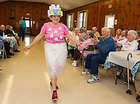 "The Friendship Club's Fashion Show features Carole Veer taking the runway in a wrap around skirt and a pretty loose ""tea"" shirt.  Completing her outfit is a ""pill box"" hat made popular by Jackie Kennedy during the 1960's.  (Karen Bobotas/for the Laconia Daily Sun)"