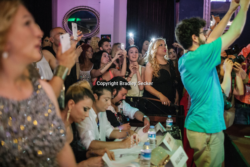 Spectators and jury members (seated centre) watch the participants in Istanbul's second Trans beauty pageant, held at The Mekan. The women had both swimwear and evening gown shows for the judges.