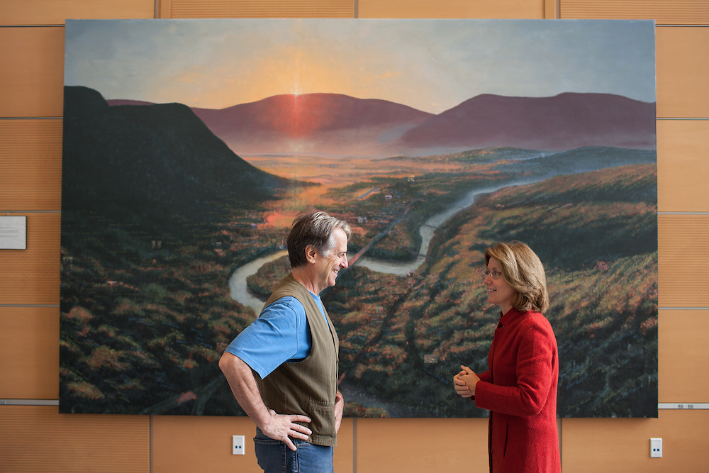Mass College of Liberal Arts president Mary Grant (R) talks with internationally known artist Steve Hannock, in front of Hannock's painting that hangs in the atrium of the Feigenbaum Center for Science and Innovation, in North Adams on Thursday, October 10, 2013. The long-struggling mill town of North Adams has been revitalized by an infusion of art and artists, encouraged by the state college there and city itself. As a result, hundreds of artists now call it home.  (Matthew Cavanaugh)