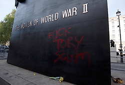 """© London News Pictures. 09/05/2015. The words """"FUCK TORY SCUM"""" spray painted on to the Women of World War Two memorial on Whitehall following an anti austerity demonstration today (Saturday). Photo credit: LNP"""