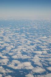 Aerial photograph of some clouds from an airplane window.
