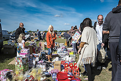 People buying and selling at a car boot sale in Essex.