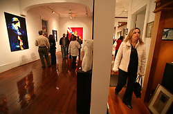 04 February, 2006. New Orleans, Louisiana.<br /> Art and money returns to the city with a Saturday night art walk in Uptown New Orleans. Wealthier residents from one of the city's more affluent neighbourhoods contemplate art at galleries along Magazine Street.<br /> Photo; Charlie Varley/varleypix.com