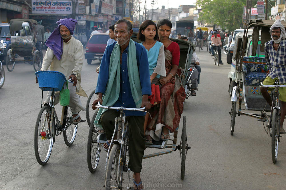 Munna Kailash a rickshaw driver ferries his wife, niece, and son on a shopping trip in  in Varanas, Utta Pradesh province, India,. (From the book What I Eat: Around the World in 80 Diets.) The caloric value of his typical day's worth of food in the month of April was 2400 kcals. He is 45 years old; 5 feet, 6 inches; and 106 pounds. India has about 10 million cycle rickshaws, including passenger and cargo pedal carts. Although Munna owns his rickshaw, most rickshaw pullers rent from fleet owners for about $0.60 (USD) per day. A typical puller in a big city earns about $4 to $5 (USD) per day. Although slower than two-cycle smoke-spewing auto-rickshaws, bicycle rickshaws don't pollute the air, and the only heat they add to the atmosphere is from the bodies of their drivers.