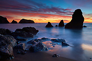 A fiery sunset stretches across Rodeo Cove, reaching from the sea stacks to Bird Island in the Marin Headlands near San Francisco, California. The Marin Headlands are part of the Golden Gate National Recreation Area.