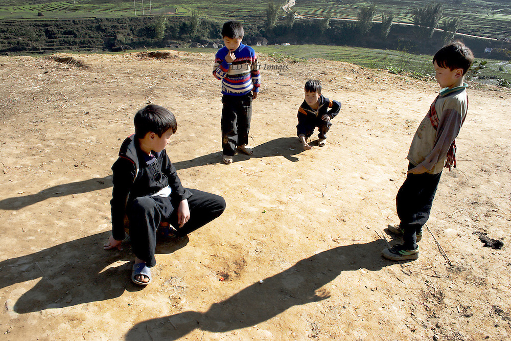 Four Hmong boys playing marbles on a dirt road near SaPa, North Vietnam.  In the afternoon sun, their figures cast sharp shadows on the road. One is about to shoot a marble into a dirt cup.  Two others watch critically.