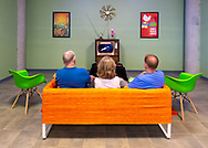 Garden City, New York, U.S. July 25, 2019. L-R, father BILL WALSH and mother KATE WALSH of Port Jefferson, and son KEVIN WALSH of Miller Place, sit on sofa in American 60s style living room, while watching CBS Apollo 11 news coverage on a tube TV set, with simulation of July 20, 1969, lunar module Moon Landing. The Cradle of Aviation Museum set was for its recent Apollo 11 Countdown on the 50th Anniversary of man first walking on the moon.