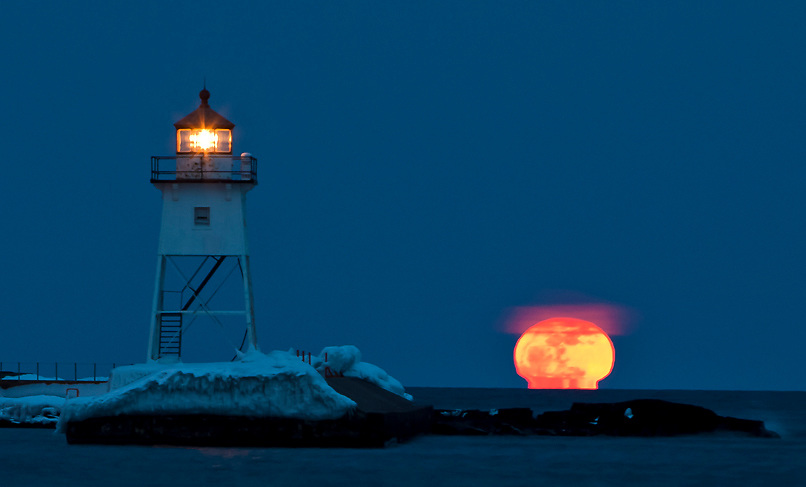Supermoon over Grand Marais Minnesota harbor with Lighthouse