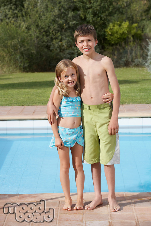 Portrait of sister and brother (6-11) by pool smiling